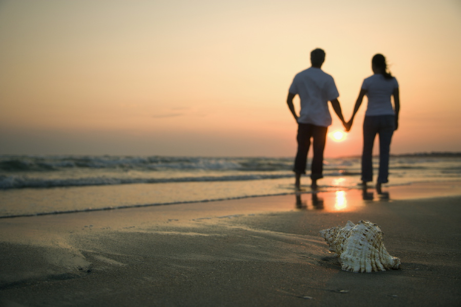 Man and Woman on beach holding hands
